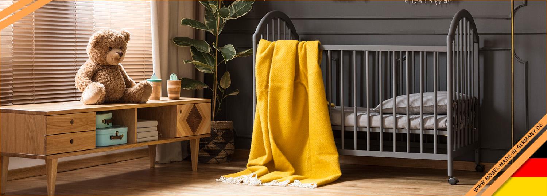 Kinderzimmer mit einem schwarzem Kinder Gitterbett